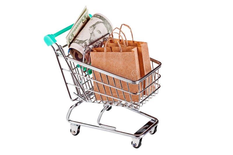 Вагонетка покупок при бумажные сумки и доллары изолированные на белизне стоковые изображения