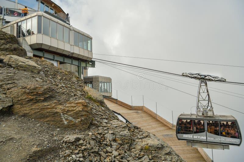 Вагон подвесной дороги переполнятьый туристами причаливая верхней станции на верхней части стоковое изображение