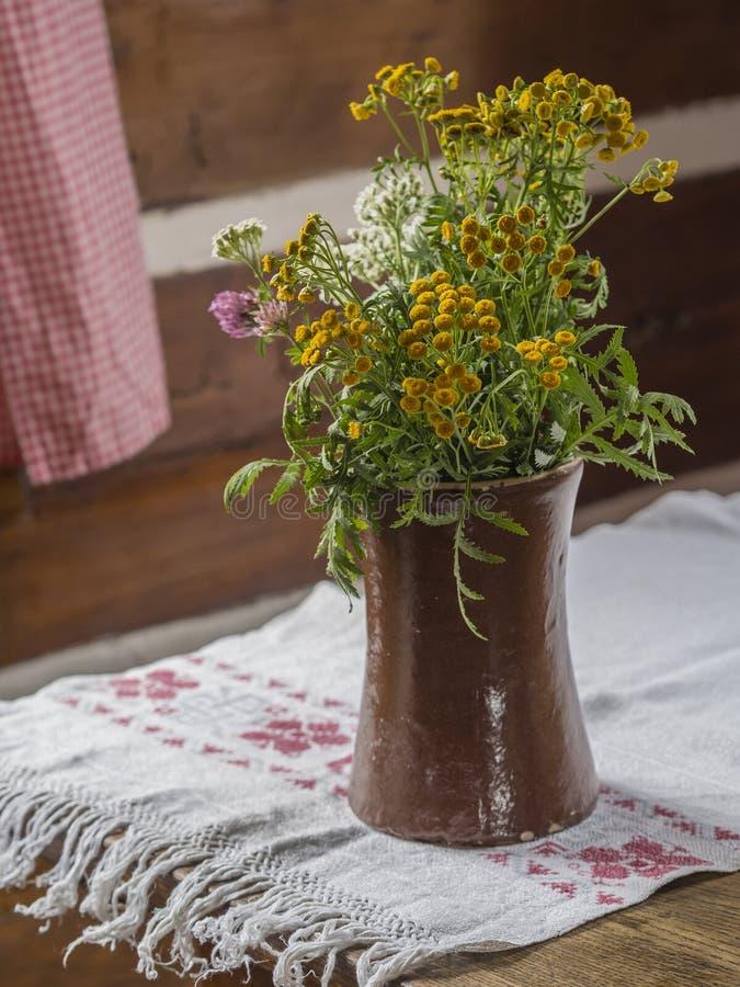 Ваза Брайна керамическая с желтым белым и розовым полем цветет дальше стоковое фото