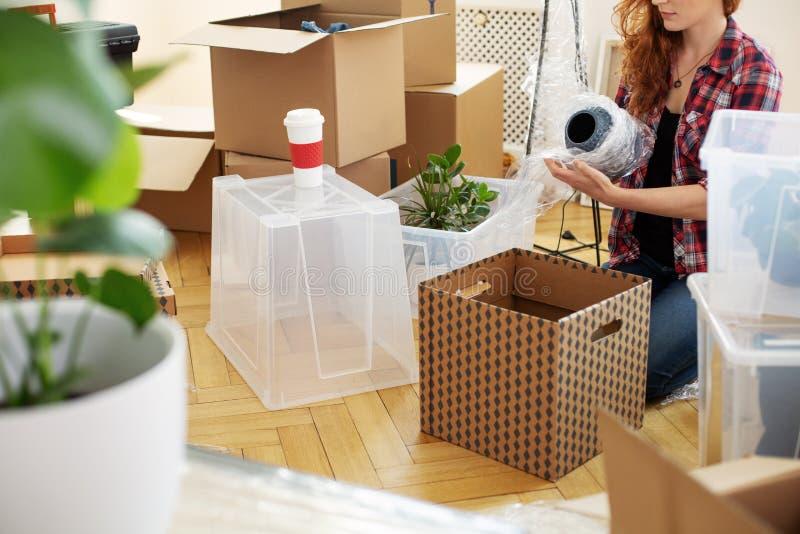 Ваза женщины защищая с фольгой пока пакующ вещество в коробки после перестановки стоковая фотография