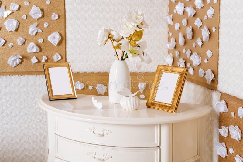 Ваза с цветками и рамками фото на таблице в белой и золотой спальне Натюрморт, детали украшения комнаты стоковые фотографии rf