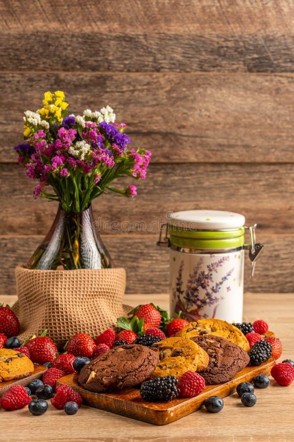 Ваза цветка с дикими ягодами и печеньями шоколада на борту стоковые изображения rf