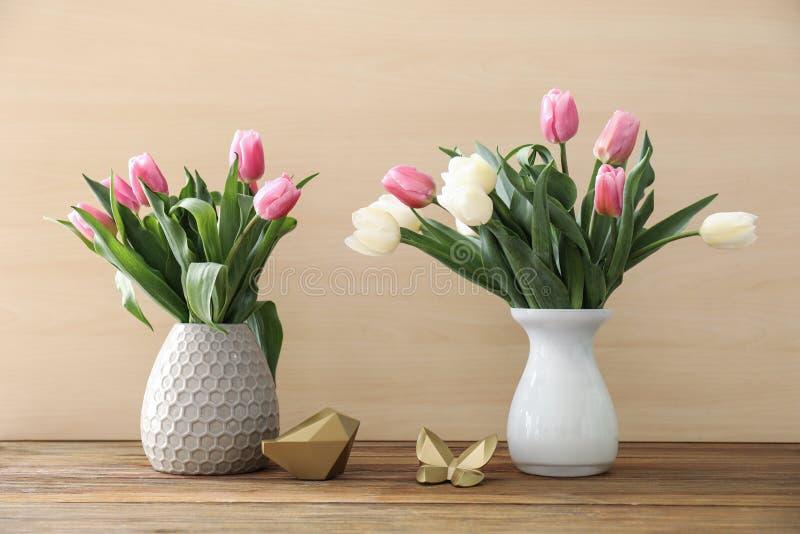2 вазы с красивыми тюльпанами на деревянном столе стоковая фотография