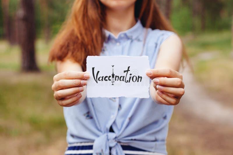 Вакцинирование - молодая женщина держа карту бумаги со словом, здравоохранением и медициной стоковое изображение rf