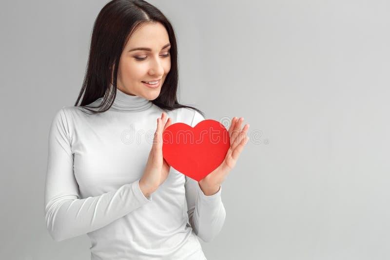 Валентайн дня s Положение женщины изолированное на серый смотря усмехаться карты сердца задумчивый стоковые изображения rf