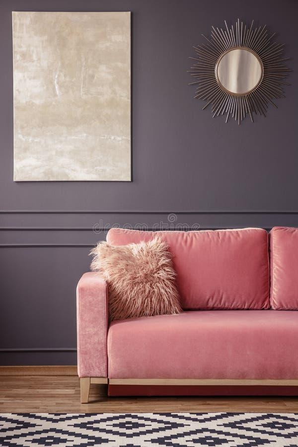 Валик меха на розовых кресле, картине и зеркале на стене и стоковые фото