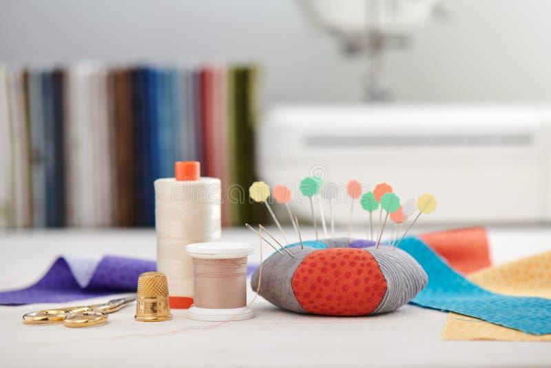Валик Pin, ярко покрашенные прокладки ткани, шить аксессуары на предпосылке стога тканей и швейная машина стоковая фотография