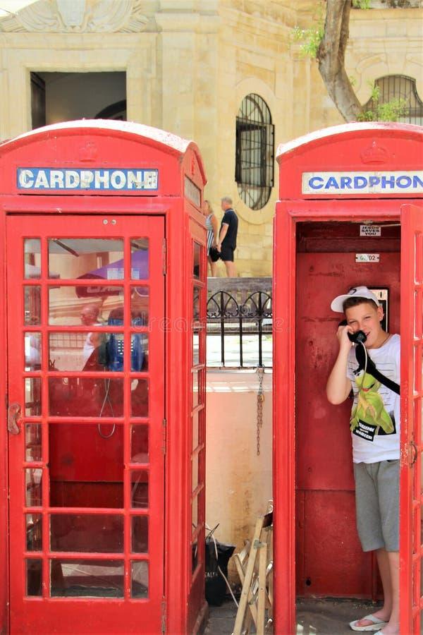 Валлетта, Мальта, июль 2016 Жизнерадостный мальчик говорит по телефону в типичной английской переговорной будке стоковая фотография