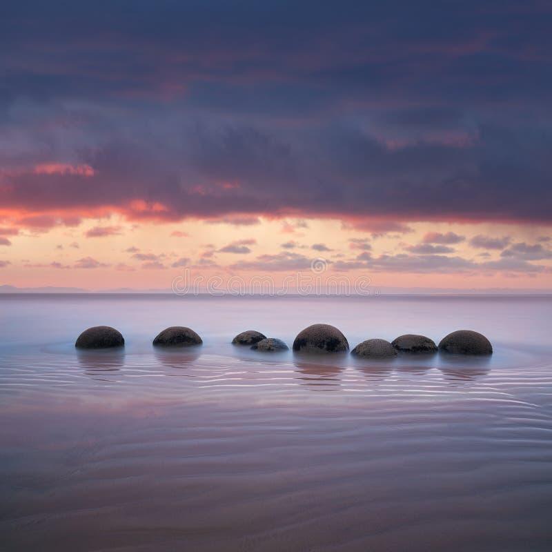 Валуны Moeraki на Koekohe приставают к берегу, восточное побережье Новой Зеландии Заход солнца и долгая выдержка и драматическое  стоковая фотография rf