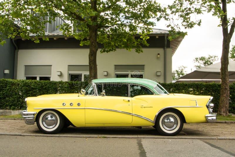 ВАЛЬДОРФ, ГЕРМАНИЯ - 4-ОЕ ИЮНЯ 2017: Экстренныйый выпуск 1955 Buick цвета лимонножелтых и мяты на улице Вальдорфа стоковые фото