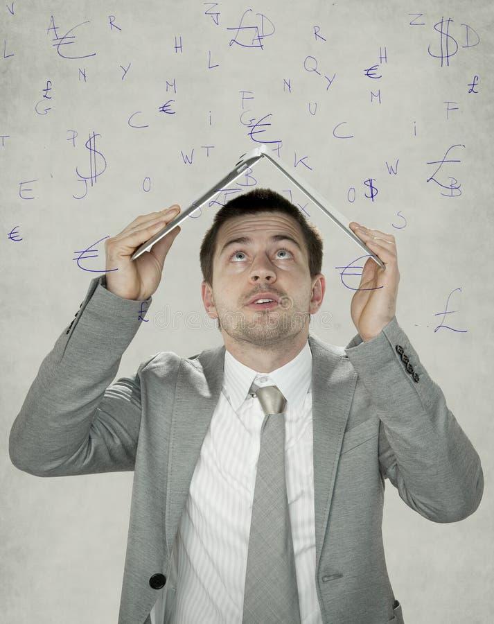 Валюты дождя, бизнесмен пряча под компьтер-книжкой стоковая фотография