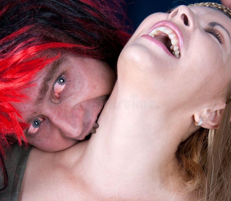 вампир сдерживая молодую красивейшую женщину стоковые фото