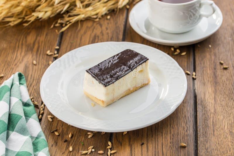 Ванильное суфле с темной поливой шоколада и чашка чаю на деревянном столе стоковое изображение