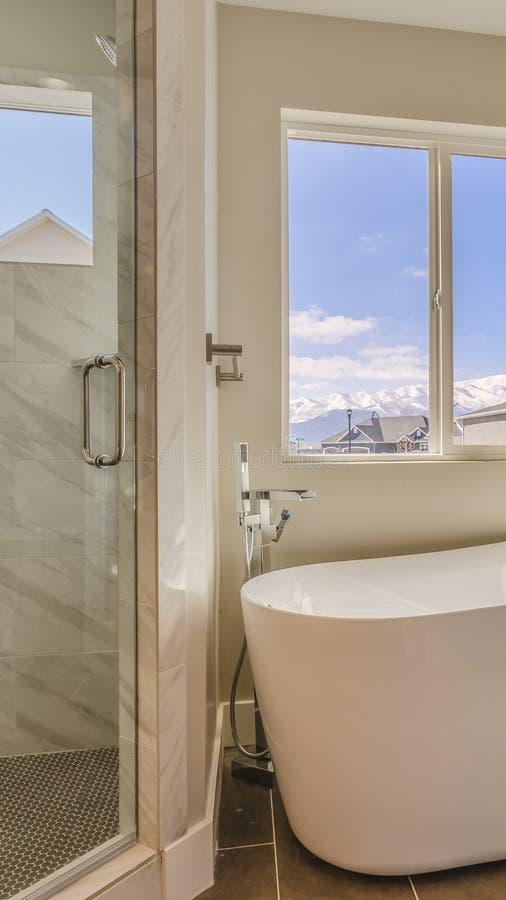 Ванна вертикальной рамки лоснистая и отдельный ливень внутри sunlit bathroom нового дома стоковое изображение