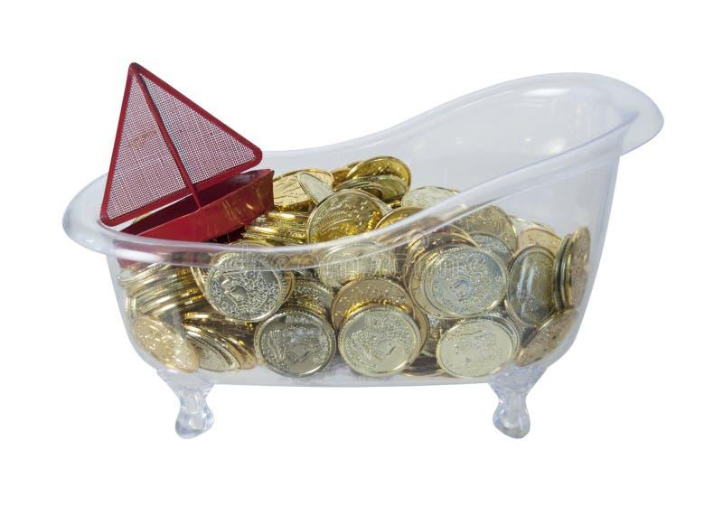 Ванна заполнила с золотыми монетками и красной шлюпкой стоковое изображение