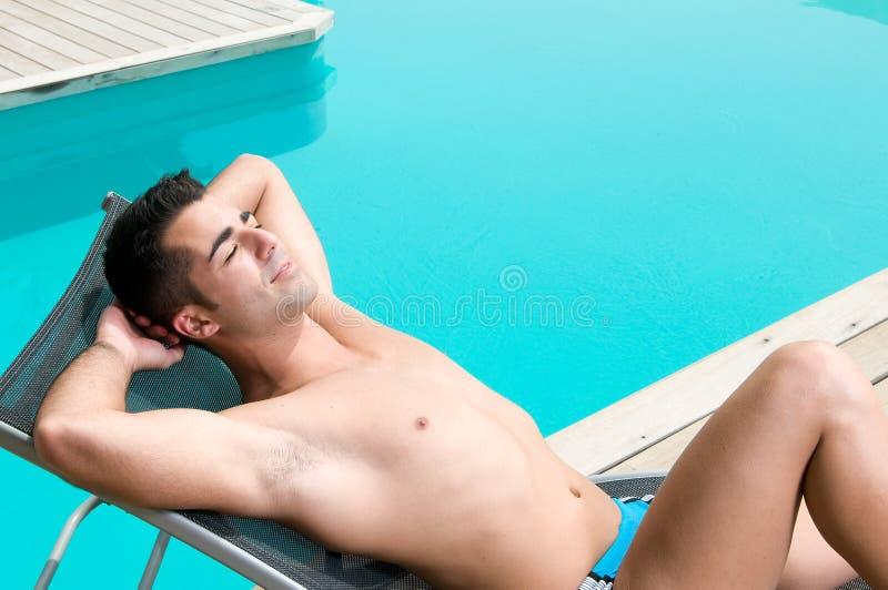 ванна имея человека около заплывания солнца бассеина стоковое изображение