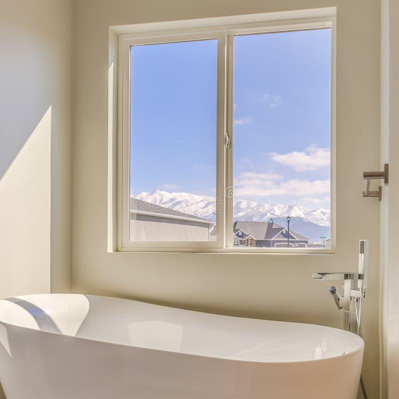 Ванна квадратной рамки лоснистая и отдельный ливень внутри sunlit bathroom нового дома стоковая фотография