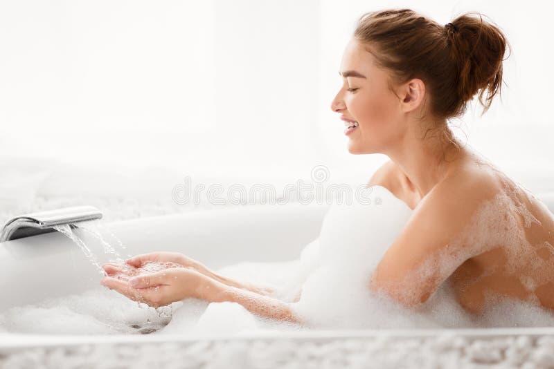 Ванна милой женщины заполняя с водой, космосом экземпляра стоковые изображения rf