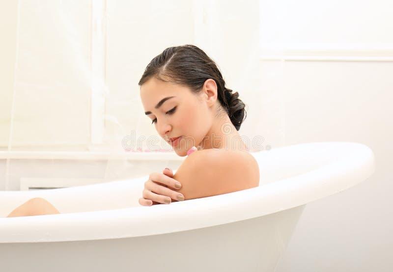 Ванна молодой красивой женщины расслабляющая стоковая фотография