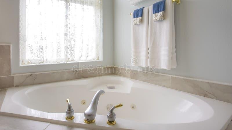 Ванна панорамы с с золотом и серебряным faucet около сдобренного окна с занавесом стоковые изображения rf