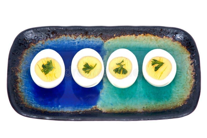 Вареные яйца с петрушкой на плите стоковое изображение
