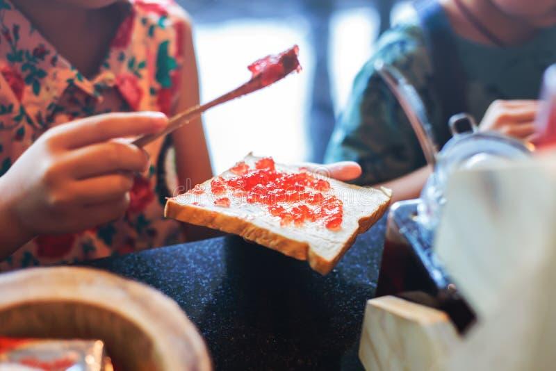 Варенье клубники ковша руки делая для завтрака стоковое фото rf