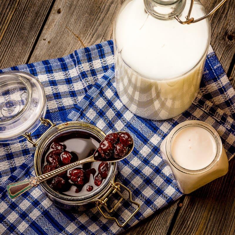 Варенье молокозавода и вишни на голубой салфетке Стиль деревенский стоковая фотография rf