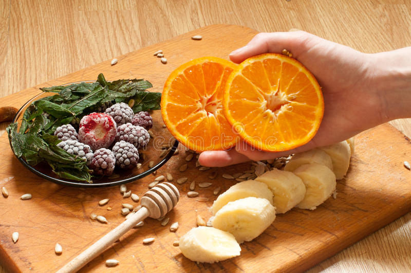 варить, банан, рука держа апельсин, который замерли ежевики клубник и ингридиенты smoothie семян яркие и blender, juicer, tul стоковое фото