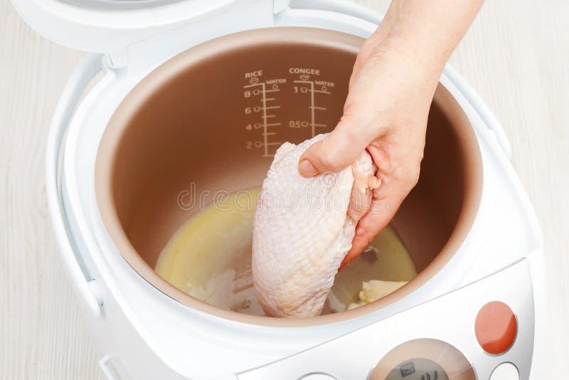 Варить бедренные кости цыпленка в multicooker стоковое изображение rf