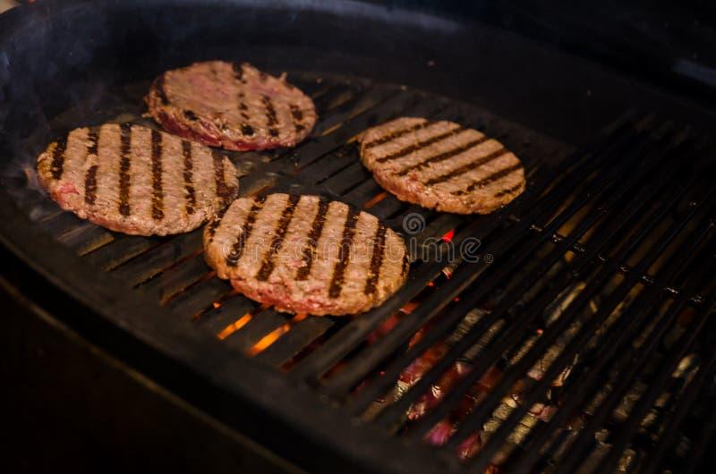 варить бургеры на горячем гриле Барбекю жечь стоковые фотографии rf
