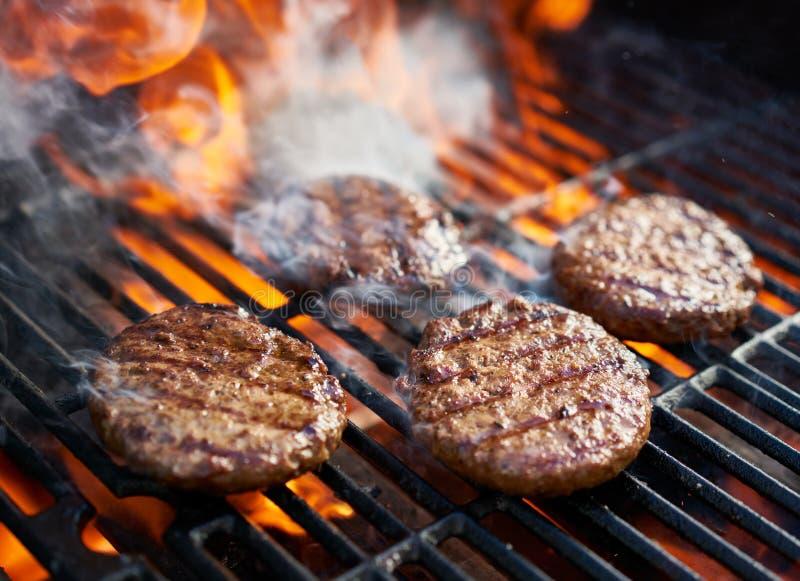 варить бургеры на горячем гриле с пламенами стоковое фото