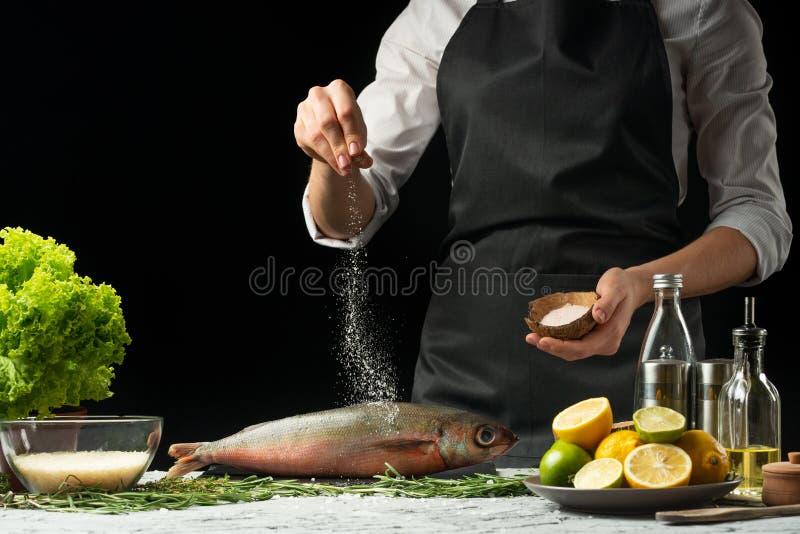 Варить вождь свежих рыб, рыбы соли шеф-повара на черной предпосылке с лимонами, известками стоковое фото