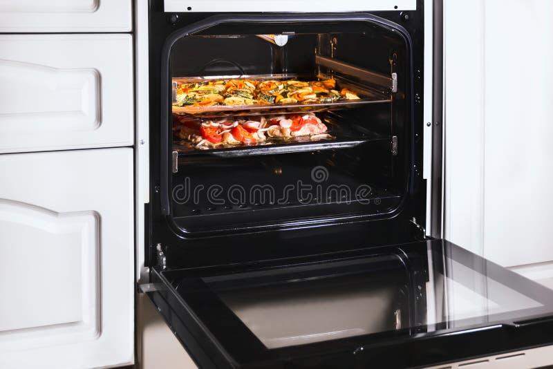 Варить еду на блюдах жарки в горячей печи стоковая фотография