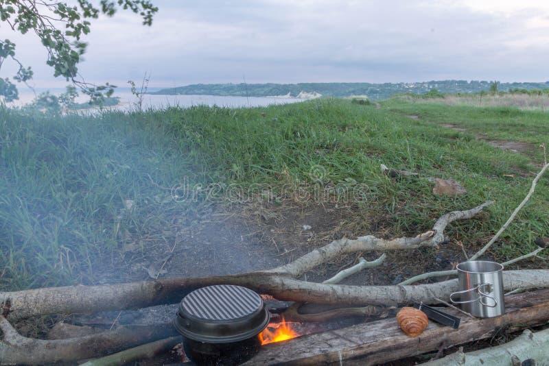 Варить еду на коле Пикник на речном береге ландшафты стоковое фото rf