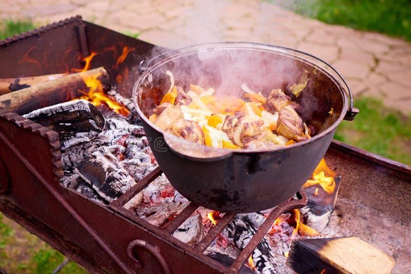 Варить мясо с овощами на огне стоковые изображения