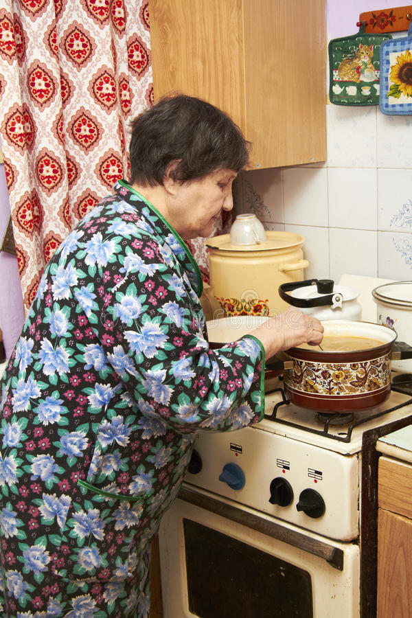 варить пожилую женщину печки супа стоковое фото