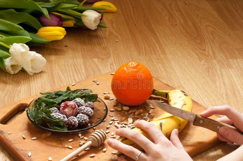 варить, рука режет банан, апельсин, который замерли ежевики клубник и ингридиенты smoothie семян яркие и blender, juicer, тюльпан стоковое фото