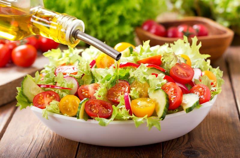 Варить салат Оливковое масло лить в шар свежего салата стоковая фотография rf