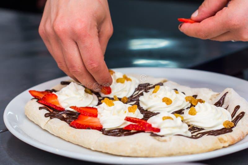 Варить сладкой итальянской пиццы Создатель пиццы рук положил дальше ягоды сливк, изюминки, клубники стоковая фотография