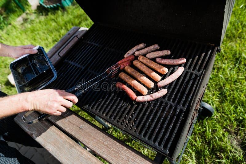 Варить сосиски мяса в барбекю Человек кладет вне еду на гриль стоковые изображения rf