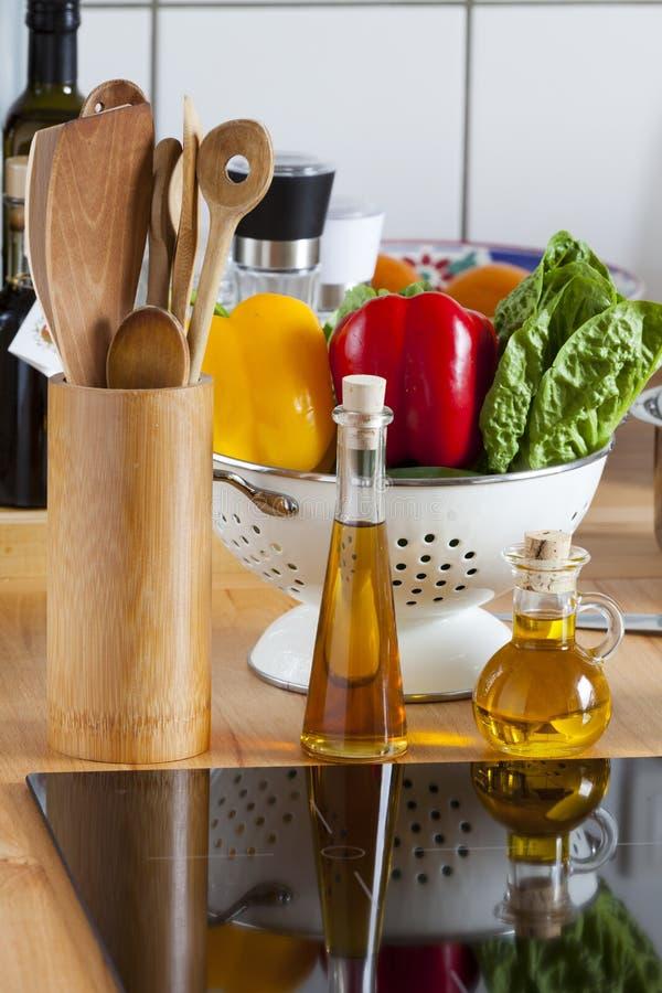 Варить шкаф, овощ, и оливковое масло ложки на Worktop стоковые изображения