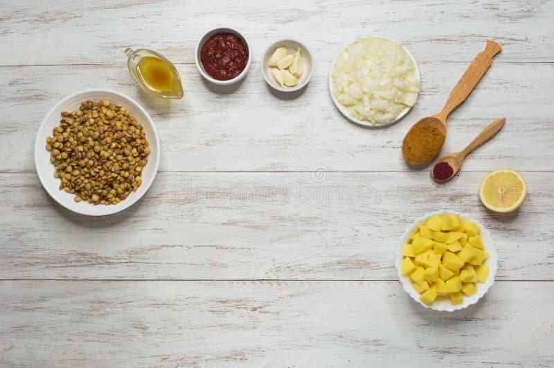 Варить Adasi, персидское тушеное мясо чечевицы Установите ингредиентов на белой таблице Аравийская еда стоковые фотографии rf