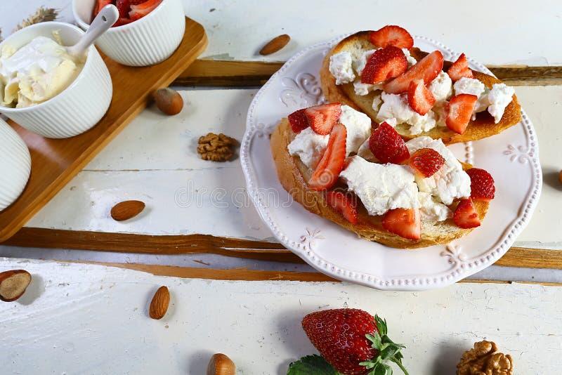 Варить bruschetta с клубникой, гайками и сыром в деревянной белой деревенской предпосылке Взгляд сверху, плоское положение, сверх стоковое изображение rf
