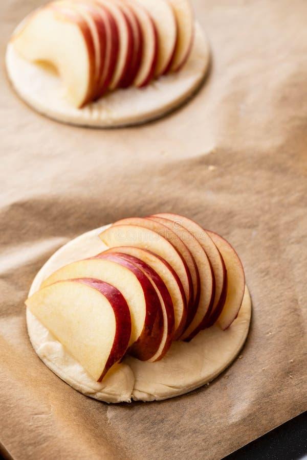 Варочный процесс galetta, печенья с яблоками на бумажной предпосылке Расстегай Apple с циннамоном стоковое фото rf
