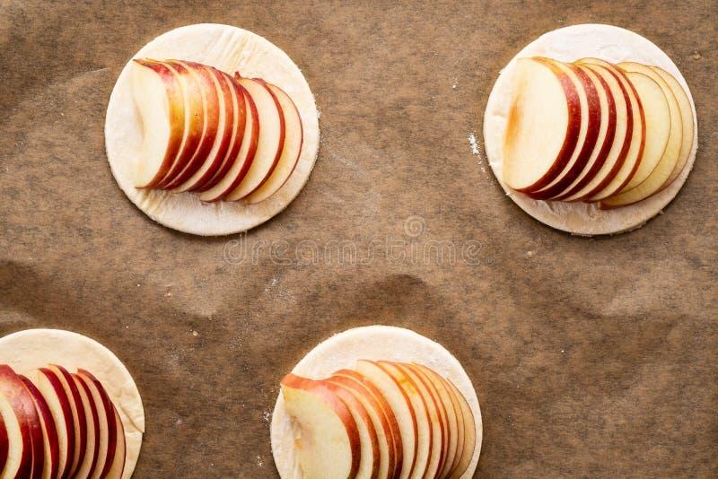 Варочный процесс galetta, печенья с яблоками на бумажной предпосылке Расстегай Apple с циннамоном стоковое изображение rf