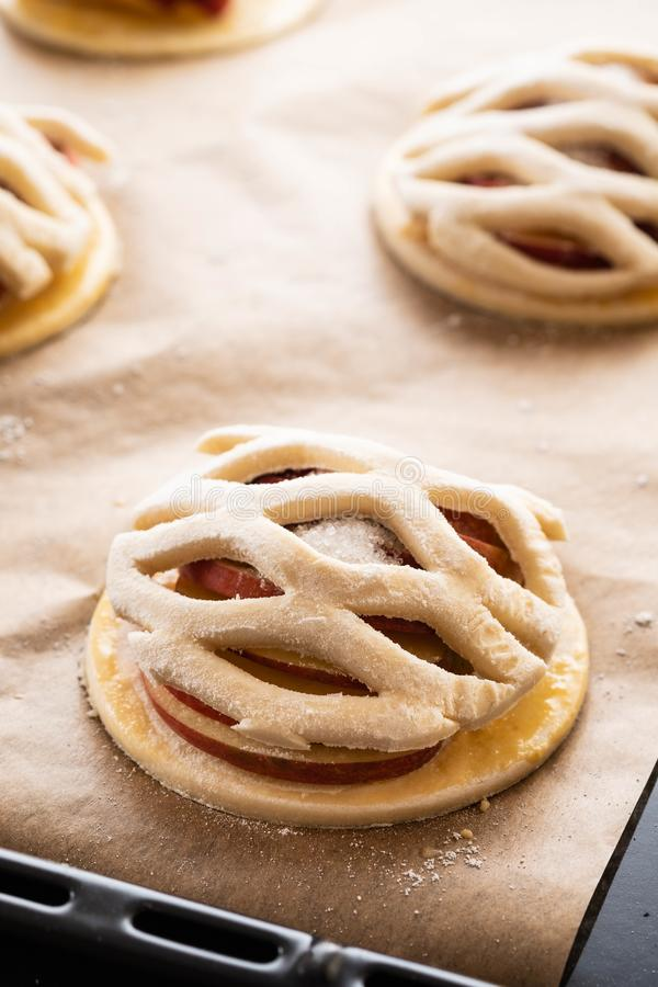 Варочный процесс galetta, печенья с яблоками на бумажной предпосылке Расстегай Apple с циннамоном стоковое фото