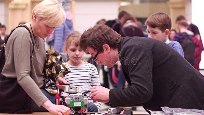 ВАРШАВА, ПОЛЬША - 4-ОЕ МАРТА 2017 Малый робот и семья DIY поддерживая молодой участника конкуренции робототехники стоковые изображения rf