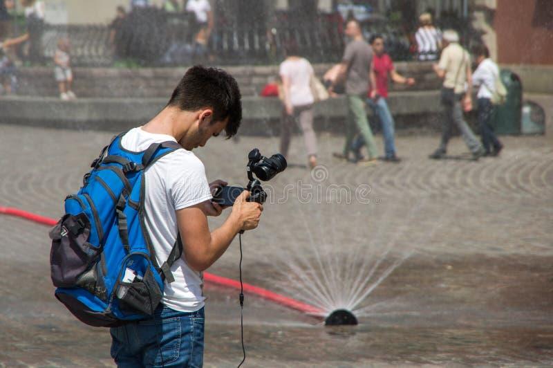 Варшава, Польша - 23-ье июня 2016 Туристы с steadicam, на фоне временного фонтана в столице Польши стоковое изображение