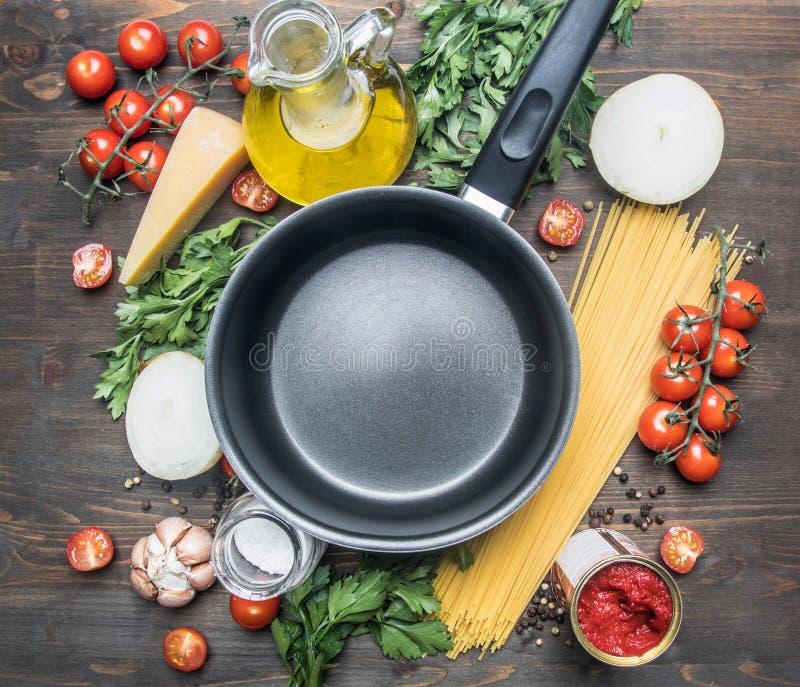 Варящ вегетарианские макаронные изделия с томатами вишни, петрушкой, луком и чесноком, маслом, сыром томатной пасты, ингредиенты  стоковая фотография