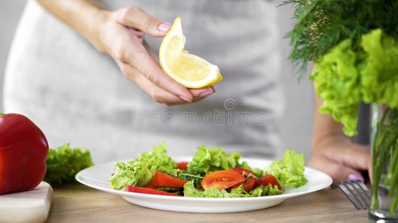 Варящ даму держа лимон соедините для заправки для салата, калорий предела, свежих продуктов стоковые фото